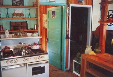 Kitchen in the cottage -- antique gas range, knotty pine, antique furnishings - at Gathering Light ... a retreat for nature lovers gathering light, a retreat offering cabins near crater lake national park and klamath basin birding trails in southern oregon. cabins, tree houses, rv camping and vacation rentals in the forest on the river near crater lake national park and klamath basin birding trails.